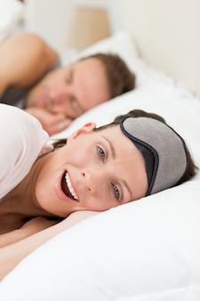 Schönes Paar in ihrem Bett liegend