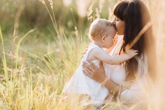 Schönes Porträt der reizend Mutter und der reizenden kleinen Tochter, die über das Feld geht