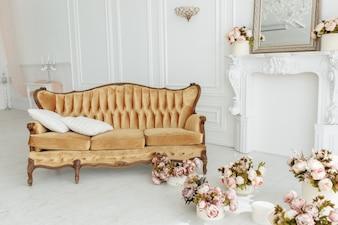 Schönes provenzalisches Wohnzimmer mit Weinlesebraun-Sofa nahe Kamin mit Blumen und Kerzen