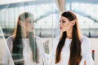 Schönheit mit dem langen Haar betrachtet ihre Reflexion im modernen Glasgebäude