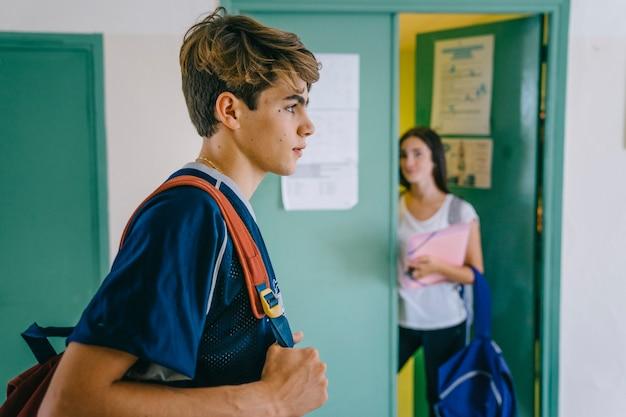 Schoolboy geht vorbei an schulmädchen