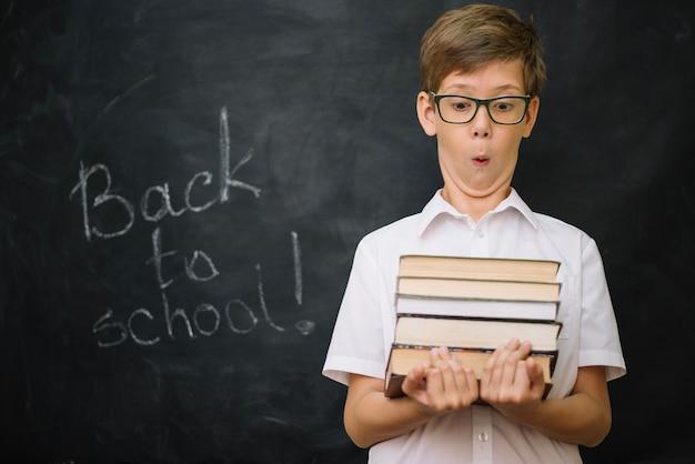 Schoolboy hält stapel von büchern stehen