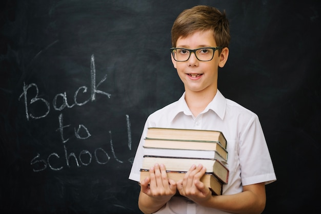 Schoolboy hält stapel von büchern