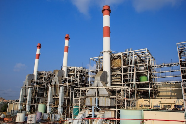 Schornstein im kraftwerk mit blauem himmel und wolken