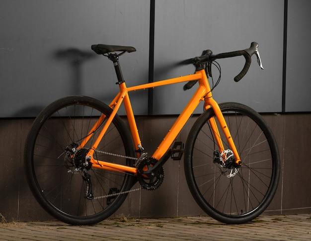 Schotterfahrrad. orange fahrrad für offrad radfahren auf grauer wand