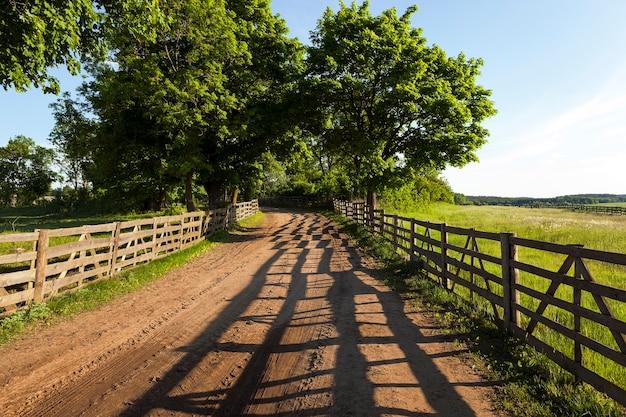 Schotterstraße im ländlichen bereich der farm. von einem holzzaun umschlossen