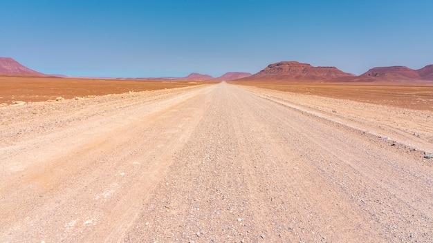 Schotterstraße in damaraland in namibia mit roten felsenbergen. von palmwag nach sprinbokwasser.