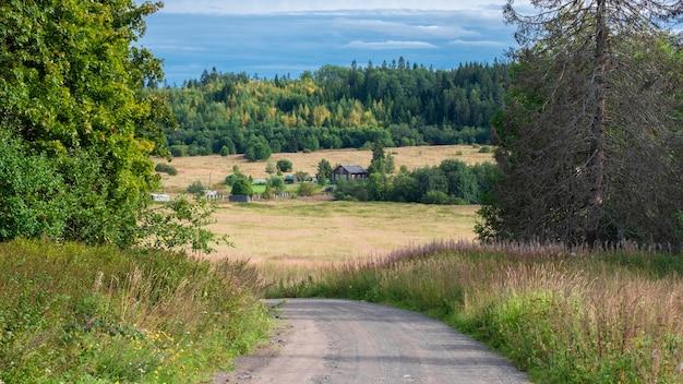 Schotterstraße zwischen feldern und wäldern, die zu einem dorf führt