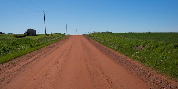Schotterweg, der durch ländliche landschaft, albany, prinz edward island, kanada überschreitet