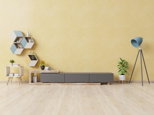 Schrank für fernsehapparat oder platzgegenstand im modernen wohnzimmer mit lampe, tabelle, blume und anlage auf gelber wand.