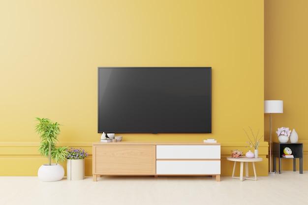 Schrank tv und gelbe wand im wohnzimmer.