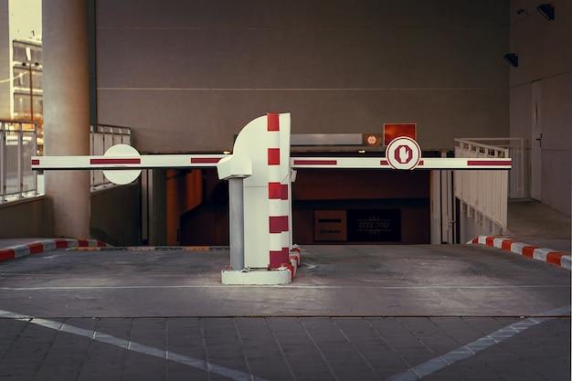 Schranke bei ein- und ausfahrt eines pkw-parkhauses. schranke auf einem parkplatz. ausfahrt aus der tiefgarage. tiefgarage, garage. innenraum des parkplatzes
