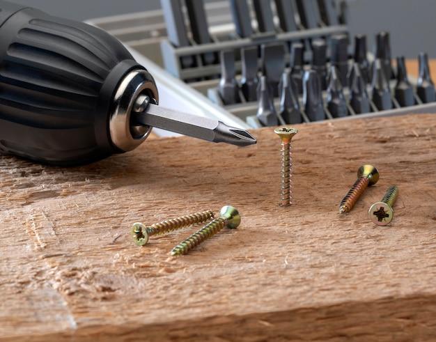 Schraube wird mit einem akku-bohrer-set in ein stück holz geschraubt. konzeptwerkzeuge und reparaturarbeiten.