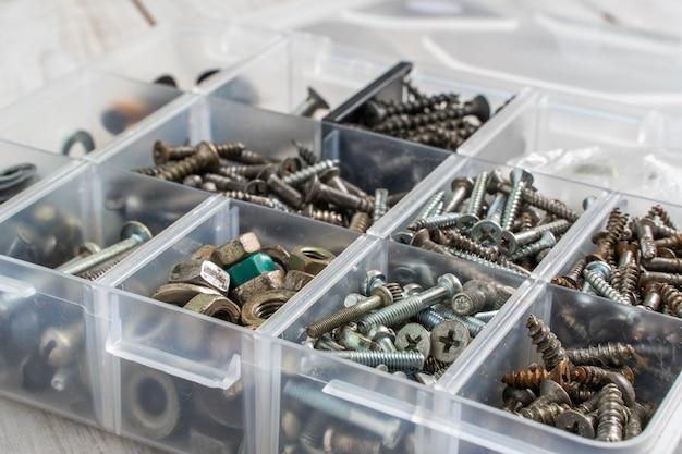 Schrauben, bolzen, muttern und anderes zimmermannszeug in einer kunststoff-werkzeugkiste (hardware-organizer). stock foto.