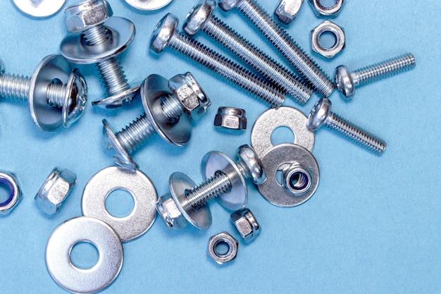 Schrauben, muttern und unterlegscheiben unterschiedlicher größe auf blauem grund.