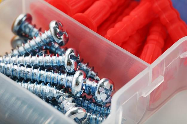 Schrauben und kunststoffdübel in verschiedenen größen für reparatur, bau und installation. nahansicht