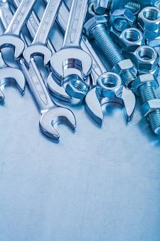 Schrauben und schraubenmuttern aus rostfreiem hakenschlüssel auf reparaturkonzept für metallischen hintergrund
