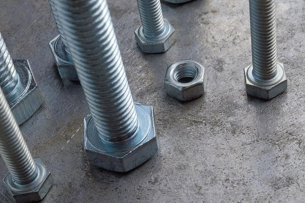Schrauben und sechskantmuttern in verschiedenen größen, ausgelegt auf einer metalloberfläche. verschiedene nahaufnahmen.