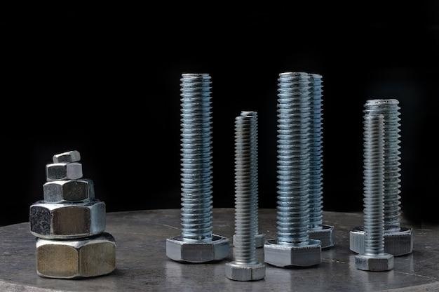 Schrauben und sechskantmuttern verschiedener größen, auf einer metalloberfläche angeordnet. verschiedene nahaufnahmen.