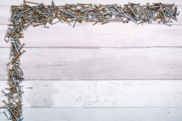 Schrauben verschiedener formen oben und an der seite eines freien raums auf einem hölzernen hintergrund. draufsicht mit platz für text