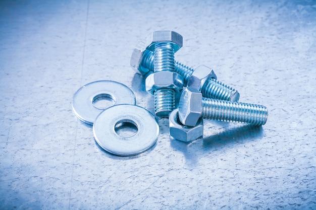 Schraubenmuttern und unterlegscheiben mit metallgewinde auf metallkonstruktionskonzept.