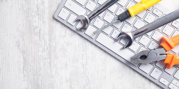 Schraubenschlüssel auf der computertastatur. it-service. unterstützung