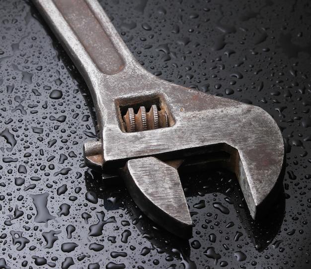 Schraubenschlüssel auf schwarz mit wassertropfen.