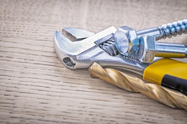 Schraubenschlüssel, bohrer und schrauben auf holzbrett