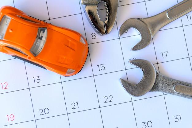 Schraubenschlüssel und auto auf dem kalender mit zahlen. reparaturkonzept