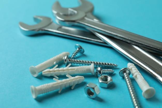 Schraubenschlüssel und dübel auf blauem hintergrund, nahaufnahme
