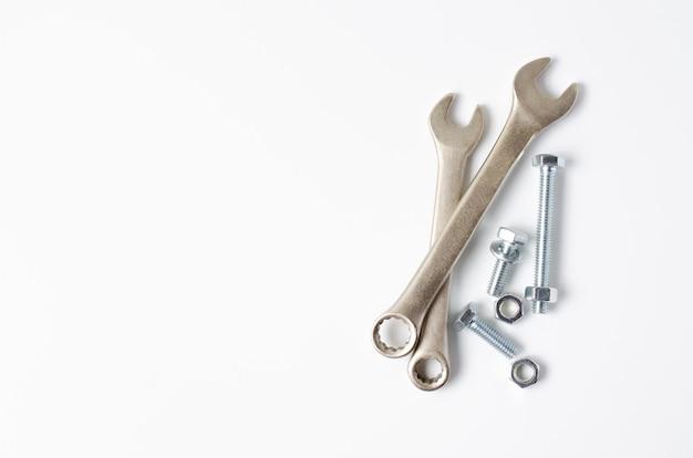 Schraubenschlüssel und schrauben mit muttern. weißer hintergrund. speicherplatz kopieren