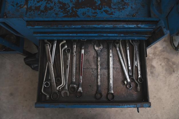 Schraubenschlüsselwerkzeuge in einer offenen schublade des alten blauen werkzeugkastens
