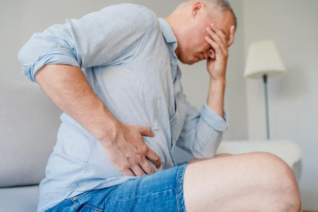Schreckliche bauchschmerzen. frustrierter hübscher junger mann, der seinen bauch umarmt und augen clo hält Premium Fotos