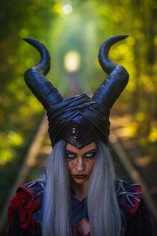 Schreckliche frau mit schwarzen hörnern silbernes haar erstaunliches make-up im tunnel des waldes mit schienen nah oben