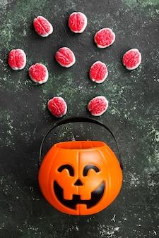 Schreckliche süßigkeiten (gehirne) für halloween im dekorativen kürbis auf einem dunklen hintergrund
