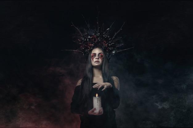 Schreckliches horror-halloween-vampir-frauenporträt. schönheitsvampirhexendame mit blut auf mund, der im tiefen wald aufwirft. modekunst design. hält eine kerze in den händen und liest flüche