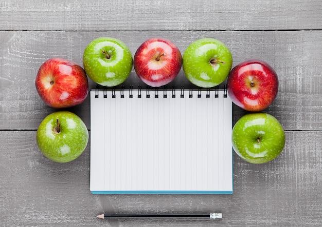 Schreibblock mit gesunden äpfeln als diätplanidee auf hölzernem brett