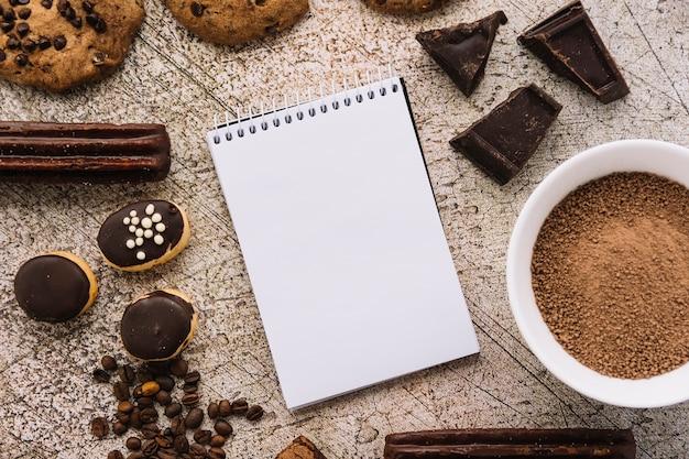 Schreibblock zwischen kaffeebohnen, keksen und schokoladenstückchen