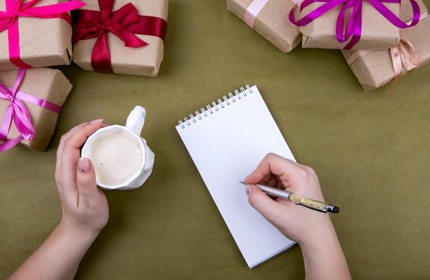 Schreibe in ein notizbuch auf dem hintergrund von geschenken