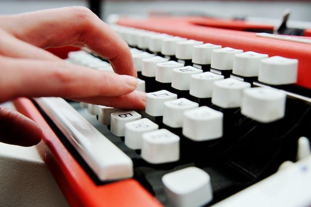 Schreiben auf vintage schreibmaschine. mädchenhände, die auf einer tastatur der alten schreibmaschine schreiben