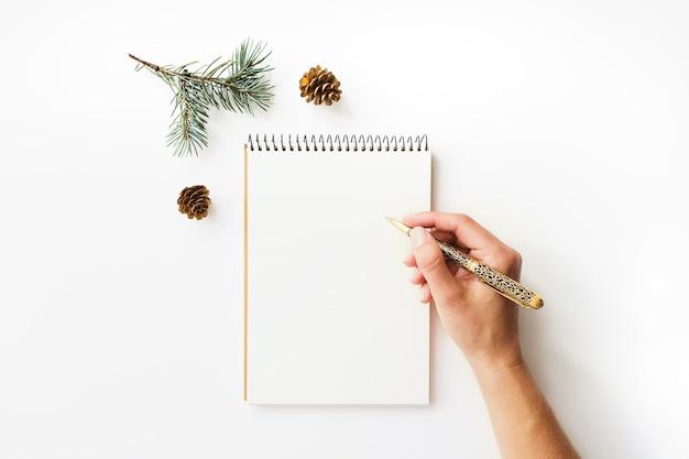 Schreiben der weiblichen hand, des papierheftes und des tannenzweigs auf weiß