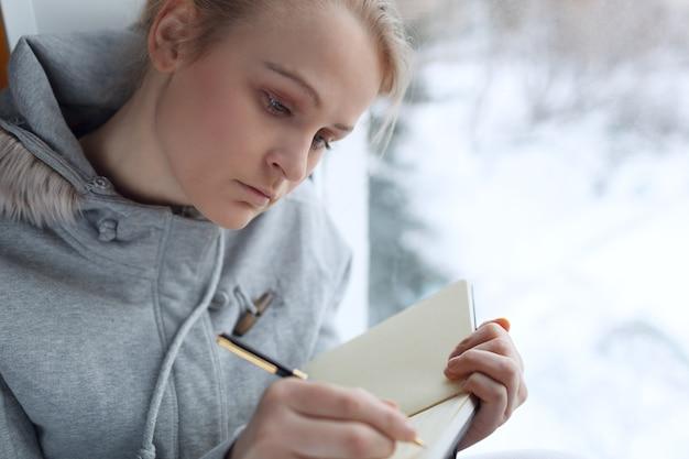 Schreiben des jungen mädchens in ihrer zeitschrift.