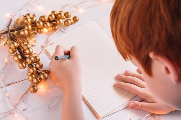 Schreiben des kleinen jungen auf notizbuch