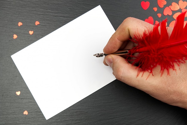 Schreiben mit buchstaben für glücklichen valentinstag, stift und rote herzformen. liebesbrief schreiben. fröhlichen valentinstag.