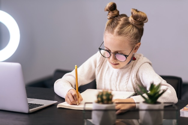 Schreiben. nettes blauäugiges langhaariges mädchen, das einen weißen pullover trägt, der etwas in ein notizbuch schreibt