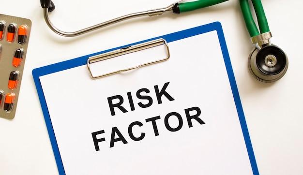 Schreiben sie den risikofaktor in den ordner mit dem stethoskop. medizinisches konzeptfoto