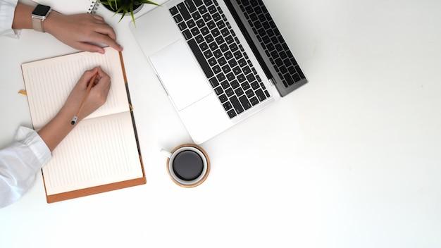 Schreibensanmerkungen der berufstätigen frau der draufsicht über notizbuch auf büroarbeitsplatz