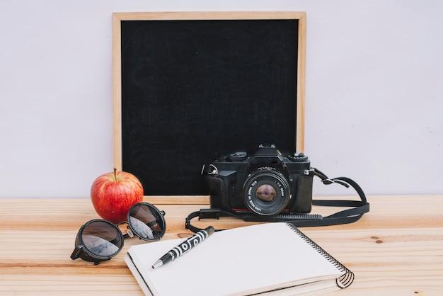 Schreibflächen in der nähe von apfel und kamera