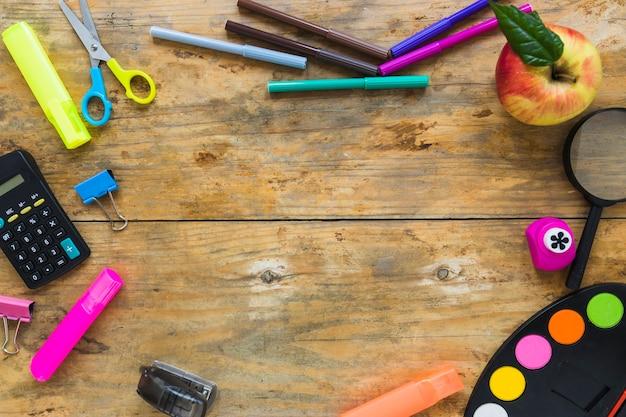 Schreibgeräte und apfel im kreis gelegt