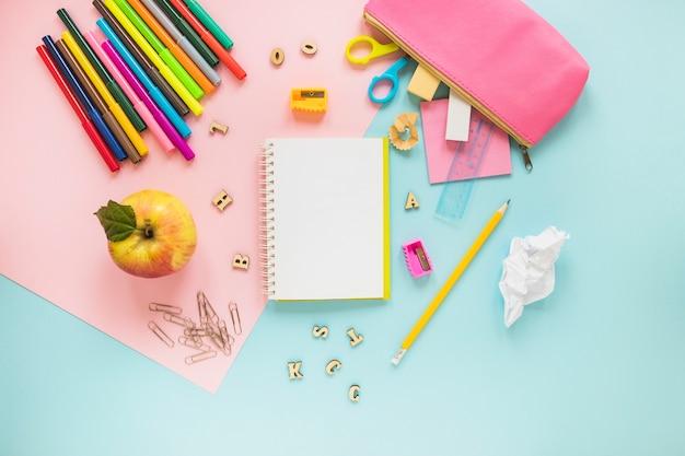 Schreibgeräte und apfel in zufälliger weise gelegt